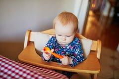 Χαριτωμένο παιχνίδι κοριτσάκι με το κουτάλι στην κουζίνα στοκ φωτογραφία
