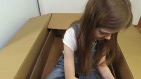 Χαριτωμένο παιχνίδι μικρών κοριτσιών με το κουτί από χαρτόνι απόθεμα βίντεο