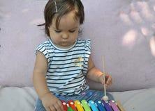 Χαριτωμένο παιχνίδι μικρών παιδιών κοριτσάκι παιδιών με το xylophone στο σπίτι Έννοια δημιουργικότητας και εκπαίδευσης πρόωρο ste στοκ φωτογραφίες