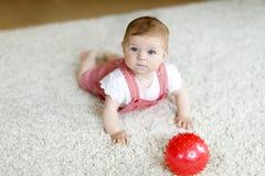 Χαριτωμένο παιχνίδι μωρών με την κόκκινη σφαίρα γόμμας Κορίτσι Lttle που εξετάζει τη κάμερα και το σύρσιμο Οικογένεια, νέα ζωή, π στοκ εικόνα