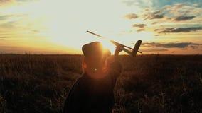 Χαριτωμένο παιχνίδι παιδιών με το ξύλινο αεροπλάνο παιχνιδιών στον τομέα στο χρόνο ηλιοβασιλέματος Σκιαγραφία του παιδιού που παί απόθεμα βίντεο