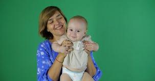 Χαριτωμένο παιχνίδι της ηλικίας γυναίκας με το παιδί 1 έτους στο στούντιο στην πράσινη οθόνη στοκ εικόνες