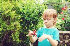 Χαριτωμένο παιχνίδι αγοριών με τον τρι Fidget κλώστη χεριών υπαίθρια Καθιερώνον τη μόδα παιχνίδι για τα χέρια για τα παιδιά και τ Στοκ φωτογραφία με δικαίωμα ελεύθερης χρήσης