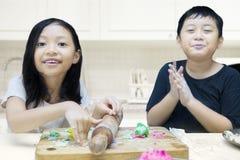 Χαριτωμένο παιχνίδι κοριτσιών και αγοριών με το playdough Στοκ Εικόνες