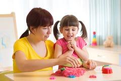 Χαριτωμένο παιχνίδι κοριτσιών και μητέρων παιδιών με την κινητική άμμο στο σπίτι Στοκ Εικόνα