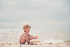 Χαριτωμένο παιχνίδι μικρών κοριτσιών με την άμμο στην παραλία στοκ εικόνες με δικαίωμα ελεύθερης χρήσης