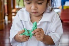 Χαριτωμένο παιχνίδι μικρών κοριτσιών παιδιών με τον άργιλο, παιχνίδι doh Στοκ Φωτογραφία