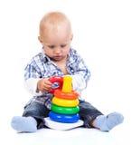 Χαριτωμένο παιχνίδι μικρών παιδιών με το παιχνίδι πυραμίδων στοκ φωτογραφία