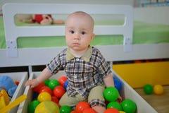 Χαριτωμένο παιδί ή παιδί που παίζει τις ζωηρόχρωμες σφαίρες που κοιτάζουν κάτω Στοκ φωτογραφίες με δικαίωμα ελεύθερης χρήσης