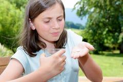 Χαριτωμένο παιδί κοριτσιών που παίρνει το χάπι με το ποτήρι του νερού Στοκ Φωτογραφία