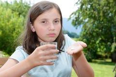 Χαριτωμένο παιδί κοριτσιών που παίρνει το χάπι με το ποτήρι του νερού Στοκ φωτογραφία με δικαίωμα ελεύθερης χρήσης