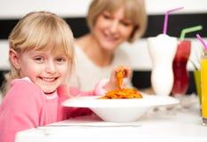 Χαριτωμένο παιδί που απολαμβάνει τα ζυμαρικά και το χυμό Στοκ εικόνα με δικαίωμα ελεύθερης χρήσης
