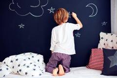 Χαριτωμένο παιδί στις πυτζάμες που χρωματίζει τον τοίχο πινάκων κιμωλίας στην κρεβατοκάμαρά του Στοκ φωτογραφία με δικαίωμα ελεύθερης χρήσης