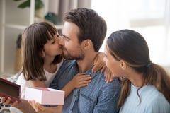 Χαριτωμένο παρόν δώρο κοριτσιών στον μπαμπά που φιλά τον στο μάγουλο στοκ φωτογραφία με δικαίωμα ελεύθερης χρήσης