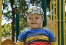 Χαριτωμένο παχύ ευρωπαϊκό αγόρι σε μια φωτογραφική διαφάνεια παιδιών ` s στοκ εικόνα