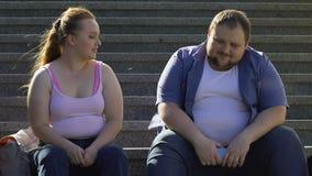 Χαριτωμένο παχύ ζεύγος που μιλά και που γελά, που κάθεται στα σκαλοπάτια, αρχή σχέσης απόθεμα βίντεο