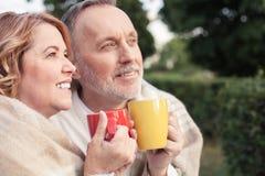 Χαριτωμένο παλαιό αγαπώντας ζεύγος στην απόλαυση του ζεστού ποτού Στοκ Εικόνα