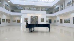 Χαριτωμένο πιάνο παιχνιδιού pianist γυναικών στην αίθουσα οπερών απόθεμα βίντεο