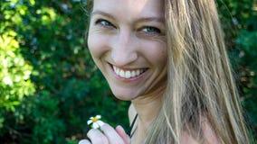 Χαριτωμένο πορτρέτο του νέου ξανθού χαμόγελου ζιζανίων λουλουδιών μαργαριτών καπνίσματος προσώπου γυναικών που γελά με τα μπλε μά στοκ εικόνα