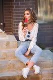 Χαριτωμένο προκλητικό brunette που φαίνεται μακριά καθμένος στα σκαλοπάτια και τρώγοντας την καραμέλα Στοκ εικόνες με δικαίωμα ελεύθερης χρήσης