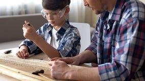 Χαριτωμένο προσεκτικό αγόρι που εργάζεται με το κατσαβίδι και το ξύλο, γιος διδασκαλίας πατέρων στοκ φωτογραφία