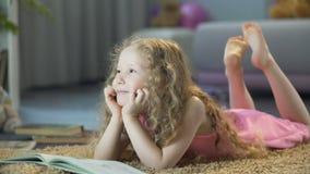 Χαριτωμένο σγουρός-μαλλιαρό κορίτσι που βρίσκεται στο μαλακό τάπητα στο σπίτι και που χαμογελά, ευτυχές παιδί απόθεμα βίντεο
