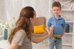 Χαριτωμένο σγουρό αγόρι που αισθάνεται τη διασκέδαση αστειεμένος με την έγκυο μητέρα Στοκ Φωτογραφίες