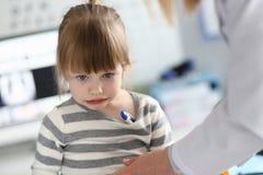 Χαριτωμένο σκεπτικό μικρό κορίτσι με το θερμόμετρο κάτω από τη μασχάλη της στοκ εικόνες