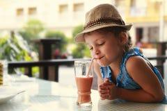 Χαριτωμένο σκεπτόμενο κορίτσι παιδιών που πίνει το νόστιμο χυμό στοκ φωτογραφία με δικαίωμα ελεύθερης χρήσης