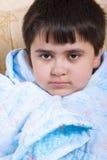 Χαριτωμένο σκοτεινός-μαλλιαρό αγόρι που τυλίγεται σε ένα blanke Στοκ φωτογραφίες με δικαίωμα ελεύθερης χρήσης