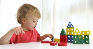 Χαριτωμένο σπίτι οικοδόμησης αγοριών στο λευκό απόθεμα βίντεο