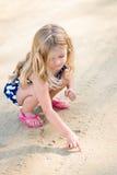 Χαριτωμένο στοχαστικό μικρό κορίτσι με μακροχρόνιο να καθίσει οκλαδόν ξανθών μαλλιών Στοκ Εικόνες
