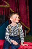 Χαριτωμένο συγκινημένο μικρό παιδί στο κωμικό κόκκινο makeup Στοκ Φωτογραφίες