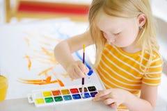 Χαριτωμένο σχέδιο μικρών κοριτσιών με τα ζωηρόχρωμα χρώματα σε μια φύλαξη Δημιουργική ζωγραφική παιδιών στο σχολείο Στοκ εικόνα με δικαίωμα ελεύθερης χρήσης