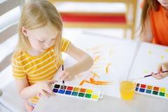 Χαριτωμένο σχέδιο μικρών κοριτσιών με τα ζωηρόχρωμα χρώματα σε μια φύλαξη Δημιουργική ζωγραφική παιδιών στο σχολείο Στοκ Εικόνες
