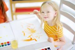 Χαριτωμένο σχέδιο μικρών κοριτσιών με τα ζωηρόχρωμα χρώματα σε μια φύλαξη Δημιουργική ζωγραφική παιδιών στο σχολείο Στοκ Φωτογραφίες