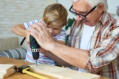 Χαριτωμένο τρυπώντας με τρυπάνι ξύλο μικρών παιδιών με Grandpa στοκ φωτογραφίες με δικαίωμα ελεύθερης χρήσης