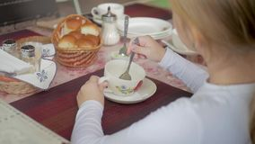 Χαριτωμένο τσάι κατανάλωσης μικρών κοριτσιών στον καφέ ελαφρύ πρόγευμα λίγο καυκάσιο κορίτσι που παίρνει μια γουλιά του τσαγιού σ απόθεμα βίντεο