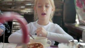 Χαριτωμένο τσάι κατανάλωσης μικρών κοριτσιών στον καφέ ελαφρύ πρόγευμα λίγο καυκάσιο κορίτσι που παίρνει μια γουλιά του τσαγιού σ φιλμ μικρού μήκους