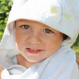 Χαριτωμένο χαμογελώντας αγοράκι στην μπλε πετσέτα Στοκ Φωτογραφία
