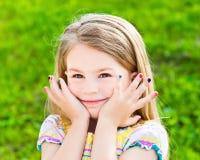 Χαριτωμένο χαμογελώντας ξανθό μικρό κορίτσι με το πολύς-χρωματισμένο μανικιούρ Στοκ φωτογραφία με δικαίωμα ελεύθερης χρήσης