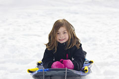Χαριτωμένο χιονιού μικρών κοριτσιών πηγαίνοντας κάτω από έναν λόφο Στοκ φωτογραφία με δικαίωμα ελεύθερης χρήσης