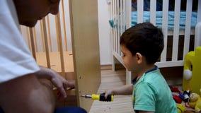 Χαριτωμένο χρονών αγόρι δύο που βοηθά τον πατέρα του στον εραστή κάτω από την κούνια για τον αδελφό μωρών του φιλμ μικρού μήκους