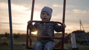 Χαριτωμένο όμορφο αγοράκι που ταλαντεύεται στην ταλάντευση στο ηλιοβασίλεμα απόθεμα βίντεο
