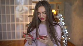 Χαριτωμένο όμορφο κορίτσι με το τηλέφωνο και την τραπεζική κάρτα που εισάγουν τον αριθμό στο εσωτερικό Εύκολος πληρώστε τη χρησιμ απόθεμα βίντεο