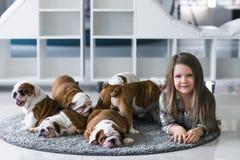 Χαριτωμένο όμορφο κορίτσι που βρίσκεται στο πάτωμα με το αγγλικό μπουλντόγκ κουταβιών Στοκ Φωτογραφίες