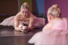 Χαριτωμένο ballerina που θερμαίνει μπροστά από τον καθρέφτη στοκ φωτογραφία με δικαίωμα ελεύθερης χρήσης