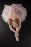 Χαριτωμένο ballerina που κάμπτει προς τα εμπρός στο ρόδινο tutu στοκ φωτογραφία