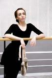 Χαριτωμένο ballerina που στέκεται κοντά στην μπάρα μπαλέτου σε έναν όμορφο Στοκ Εικόνες