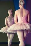 Χαριτωμένο ballerina που στέκεται στην πρώτη θέση μπροστά από τον καθρέφτη στοκ εικόνες